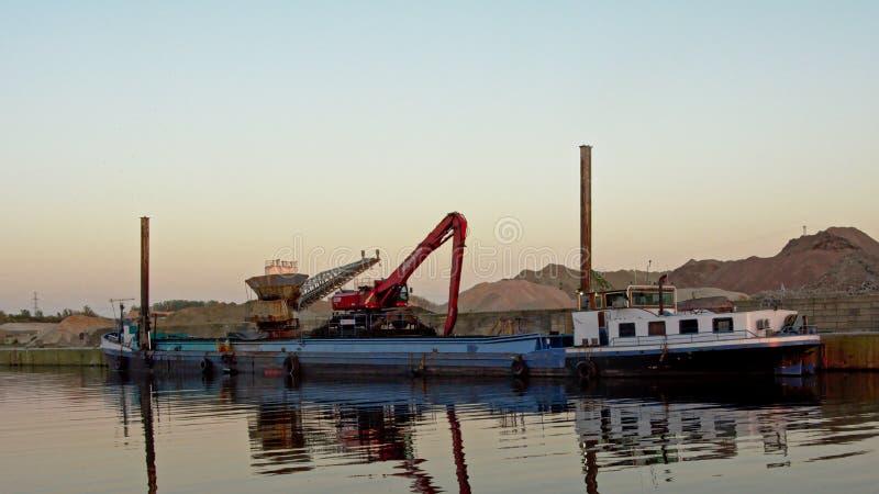 Fraktbåt bredvid en plattform i hamnen av Ghent, flanders, Belgien arkivfoto