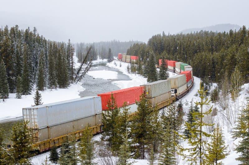 Frakter TrainRunning tillsammans med en flod under ett tungt snöfall arkivbilder