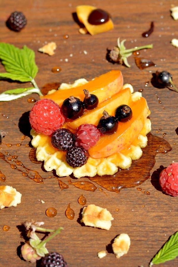 Framboesa e corinto vermelhos, pretos frescos, pêssego, gota do mel no waffle no fim de madeira do fundo acima imagem de stock