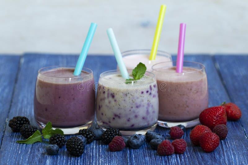 Framboesa, morango, amoras-pretas, batido do mirtilo no fundo de madeira azul Milk shake com bagas frescas Saudável foto de stock