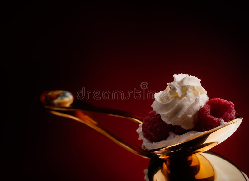 Framboesa no creme chicoteado imagem de stock