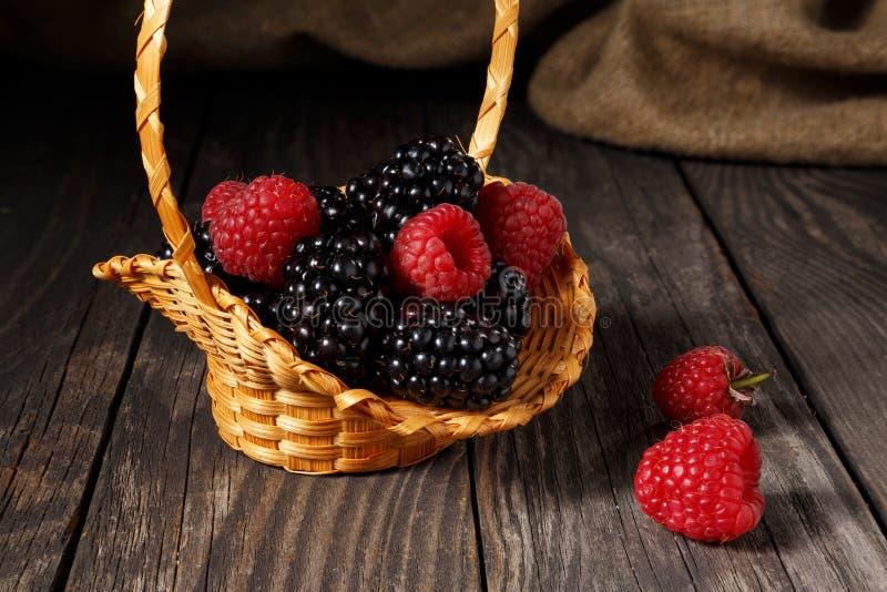 Framboesas e amora-preta em uma cesta pequena fotografia de stock