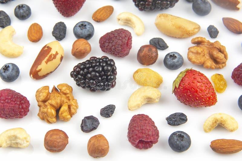 Framboesas e nozes diferentes, de fundo branco proteínas vitamínicas e alimentos saudáveis imagem de stock royalty free