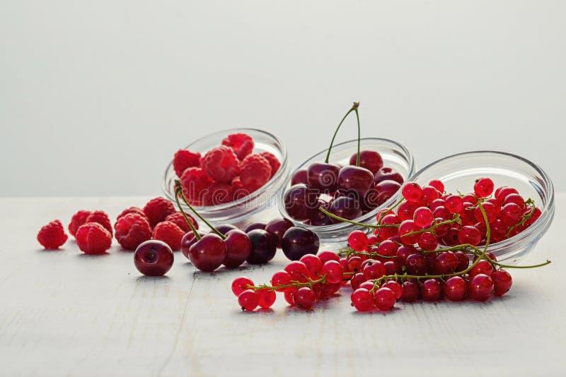 Framboesas frescas, corintos vermelhos e cerejas dispersados na tabela Foco macio fotografia de stock