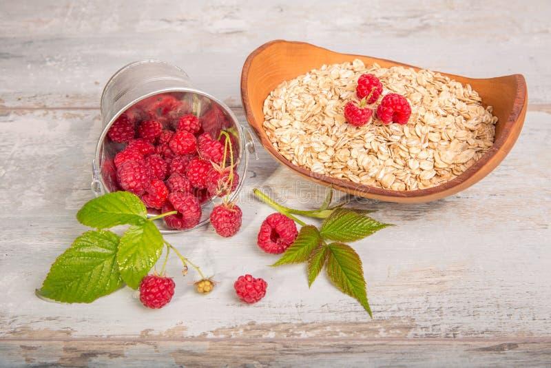 Framboesas frescas em flocos de uma cubeta e da aveia em uma bacia de madeira em um fundo de madeira rústico Dieta saudável, vege fotografia de stock