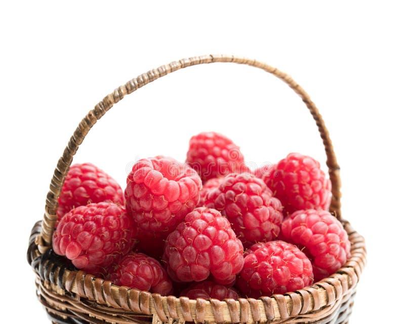 Framboesas frescas em uma cesta de vime pequena fotografia de stock