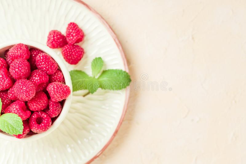 Framboesas maduras com as folhas de hortelã verdes no copo e nos pires no fundo amarelo pastel com espaço da cópia foto de stock