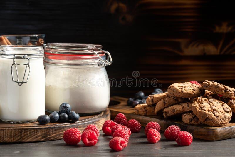 Framboesas, mirtilos e cookies caseiros colocados em bandejas de madeira imagens de stock royalty free