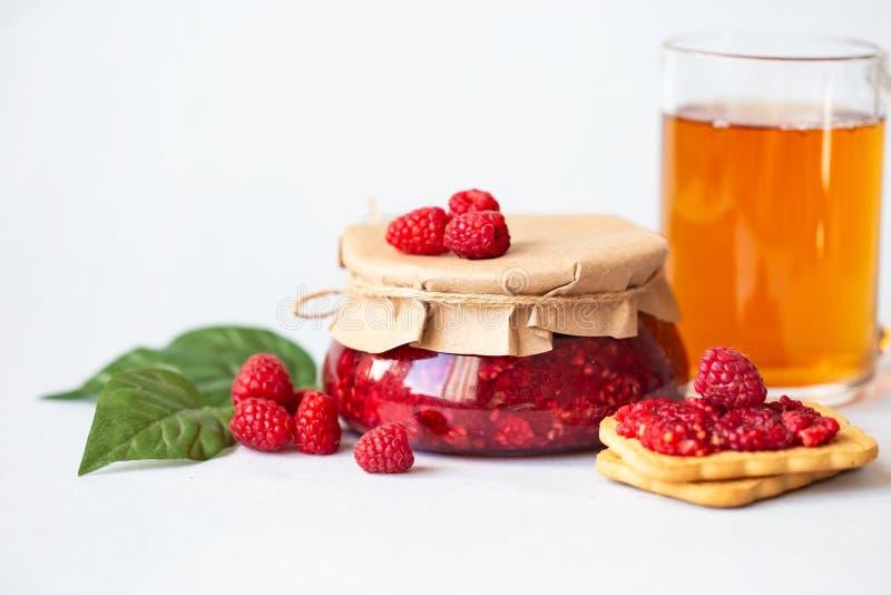 Frambozen met suiker, gezonde verse frambozen, eigengemaakte jam in een kruik, ochtendontbijt op een lichte achtergrond royalty-vrije stock foto