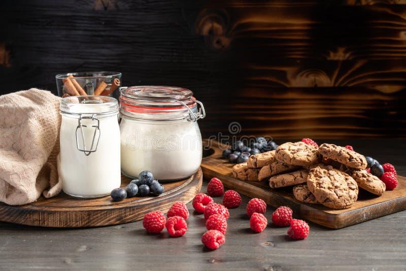 Frambozen in voorgrond, melk en koekjes in backround royalty-vrije stock fotografie