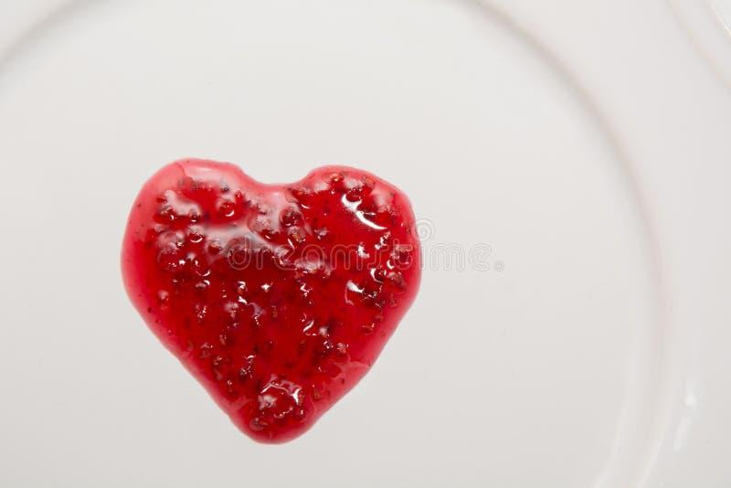 Frambozenjam in de vorm van hart op wit wordt geïsoleerd dat stock afbeeldingen