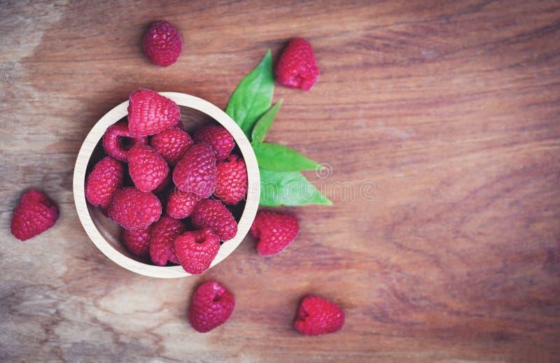 Frambuesa en cierre de madera del cuenco encima de la fruta de las frambuesas rojas y de la opinión de top verde de la hoja imagen de archivo libre de regalías