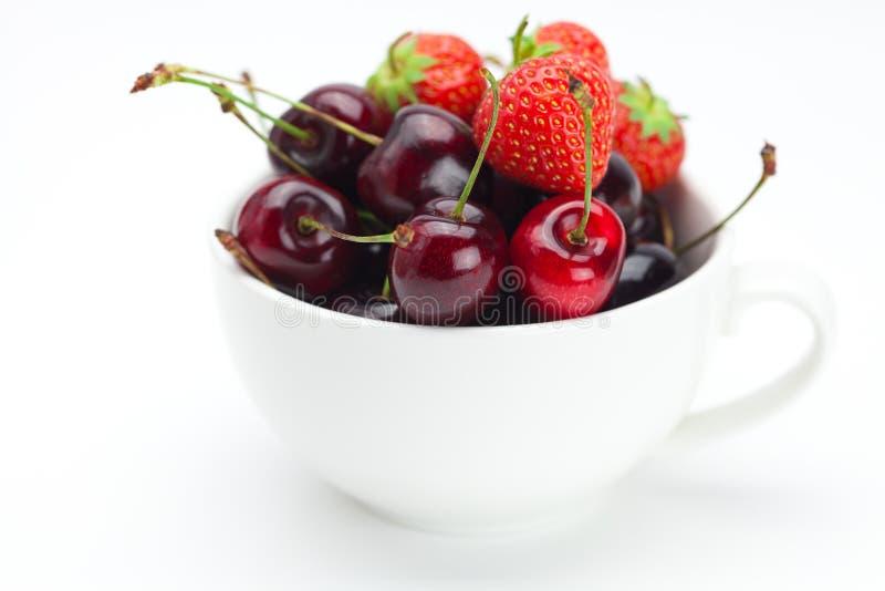 Frambuesas, fresas y cerezas en un tazón de fuente foto de archivo libre de regalías
