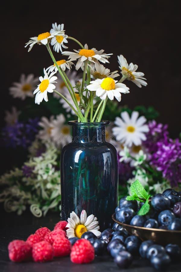 Frambuesas y arándanos con la manzanilla y las hojas en un fondo oscuro Verano y concepto sano de la comida selectivo fotos de archivo libres de regalías