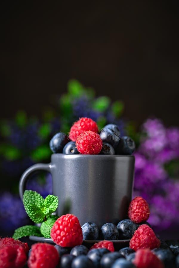 Frambuesas y ar?ndanos en una taza en un fondo oscuro Verano y concepto sano de la comida Fondo con el espacio de la copia imágenes de archivo libres de regalías