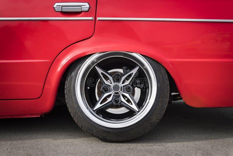 Framdel av bilen som justerar den lägre upphängningen till jordningen Sidosikt på det nya lyxiga bilhjulet på silvermetallkant me arkivbild