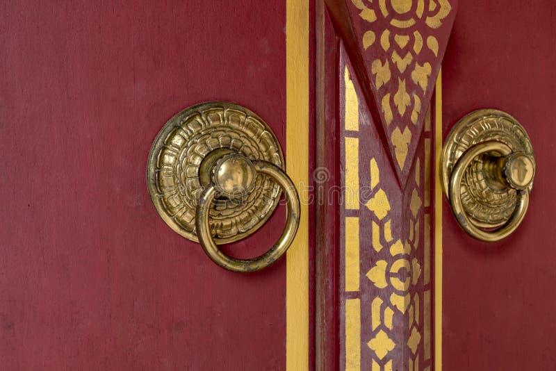 Framdel av den härliga röda trädörren till Bhutan stilbakgrund med dörrknoppen av guld- metall royaltyfri bild