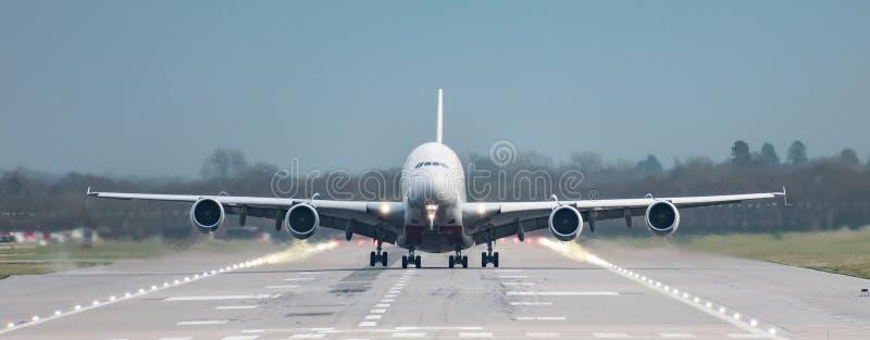 Framdel på sikten som är rak ner landningsbanan av en flygbuss för emiratflygbolag A380, som precis den tar av från den London Ga royaltyfria foton