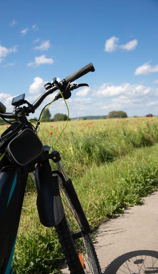 Framdelen av cykeln, hjulet av cykeln med elektriskt drev på en stenbana bredvid fältet för vårgräsplanråg med rött royaltyfri bild