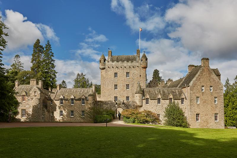 Framdelen av den Cawdor slotten med tornet och klaffbron med klocka- och fullvuxen hankronhjorthuvudbucklan är det Mindfull emble royaltyfria foton
