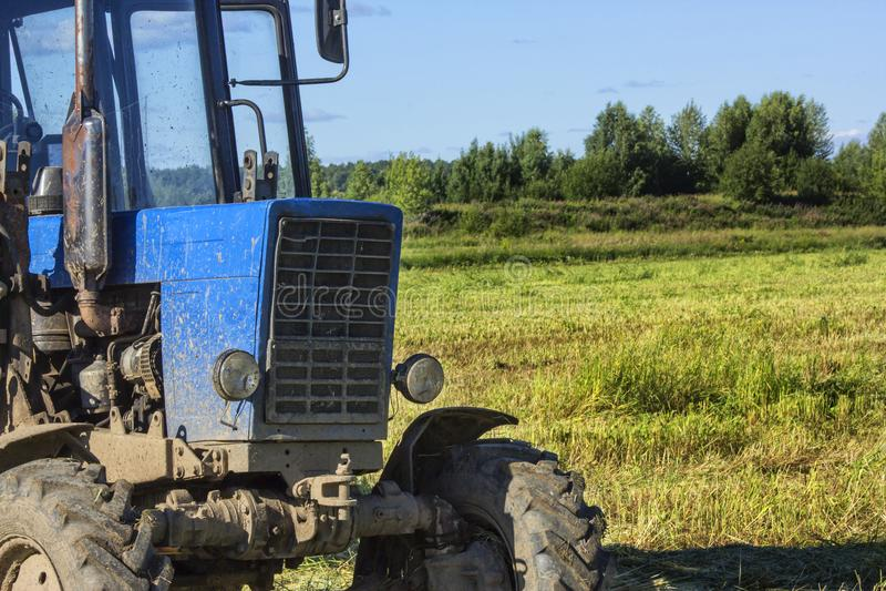 Framdelen av traktoren är stor på bakgrunden av en grön äng arkivfoton
