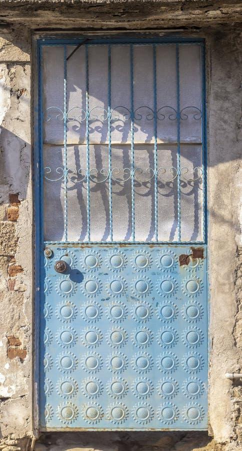 Framdelskott av den traditionella smyckade gränsen - blå metalldörr på solnedgången arkivbild