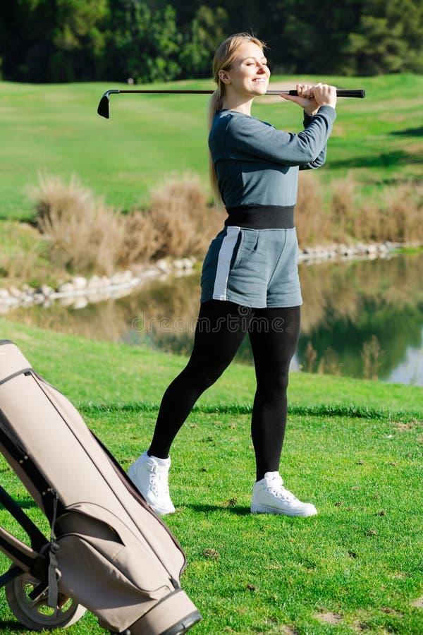 Framdriven boll för kvinna golfare lyckat på golfbanan royaltyfria bilder