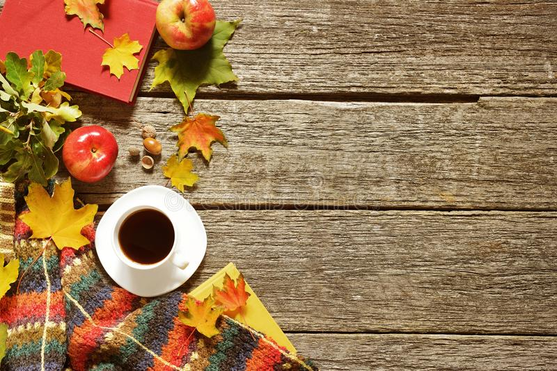 Frame of autumn red, green and yellow leaves, apples with cup of coffee or tea with books on vintage background. royalty free stock image
