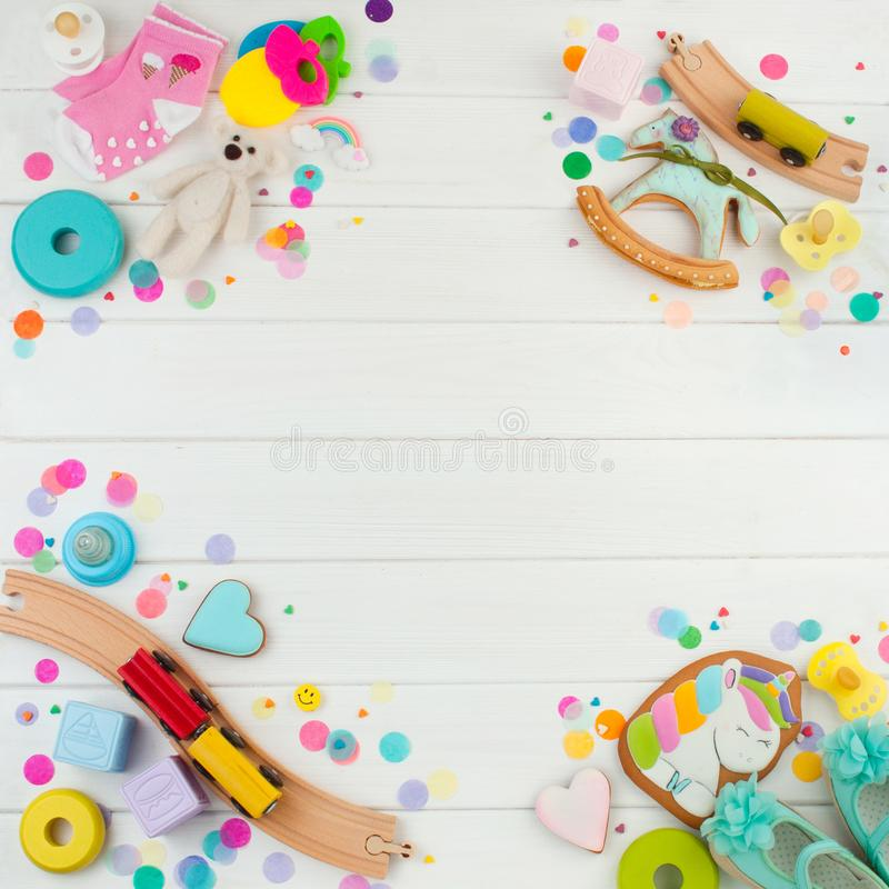 Frame from baby accessories and toys on white wooden background stock photography