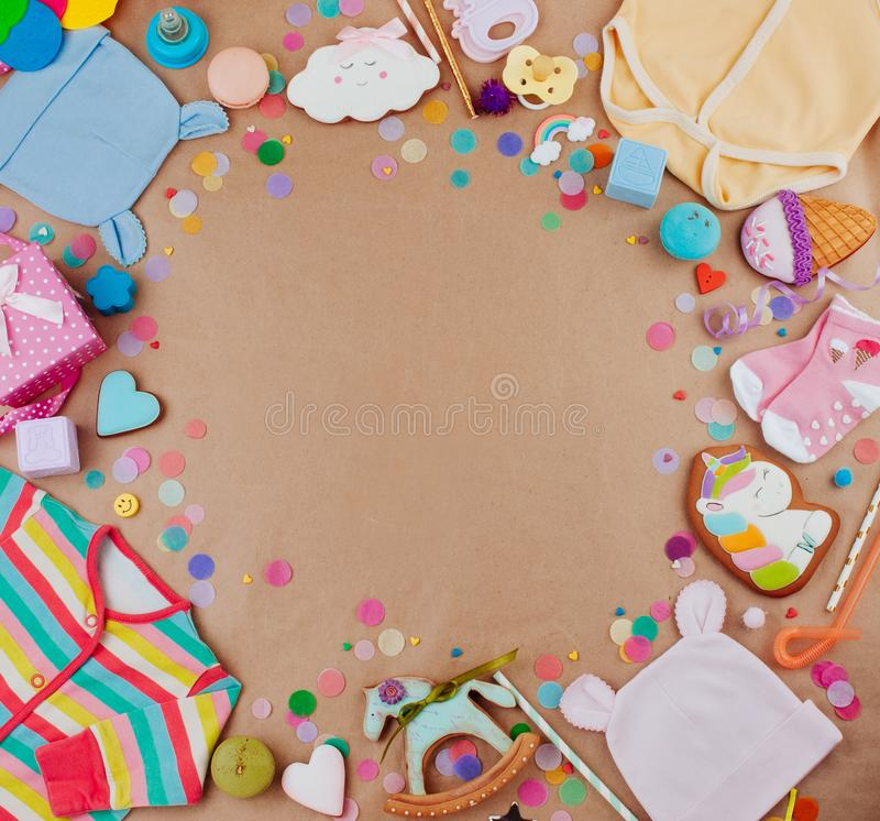 Frame of baby clothes and accessories on craft paper background royalty free stock images