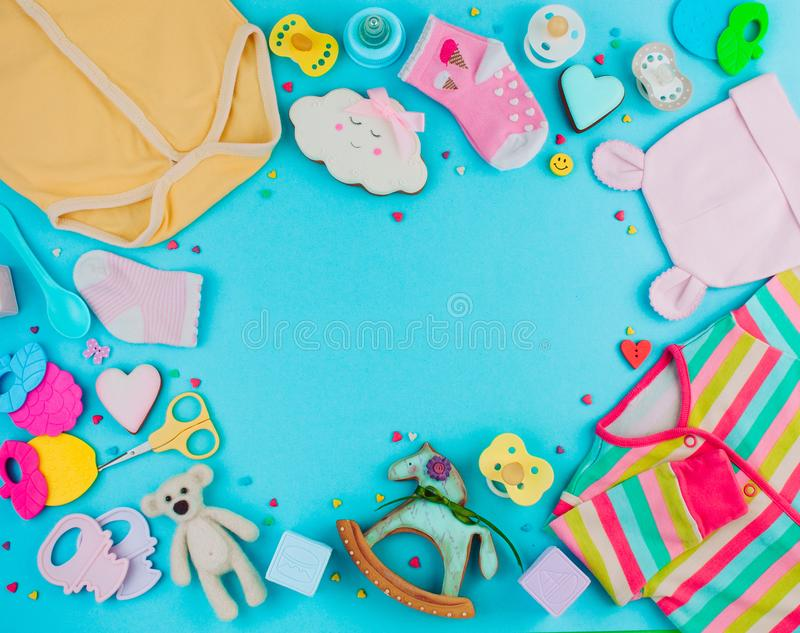 Frame of baby clothes, toys and accessories on blue background w stock images