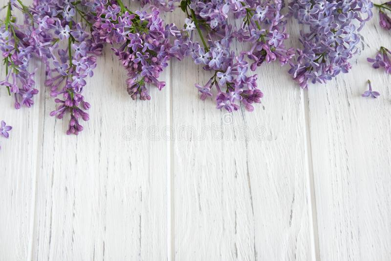 Frame for a banner of lilac flowers on a white wooden background. Background with spring flowers. The basis for a greeting card stock photography