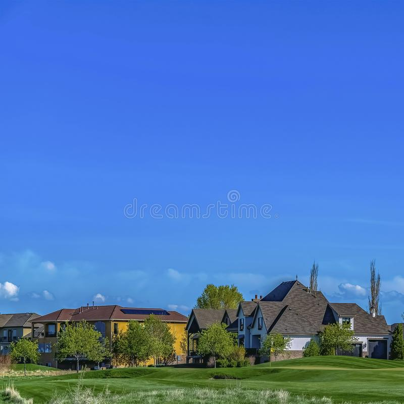 Frame Beautiful houses surrounded by lush trees and vast grassy terrain. Square frame Beautiful houses surrounded by lush trees and vast grassy terrain. Vibrant stock photography