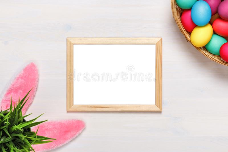 Frame, bunny ears, a flower pot with artificial green grass, colorful eggs in the basket. Easter concept. Copy space stock photography