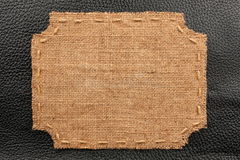 Frame of burlap, lies on a background of black leather. With place for your text stock image