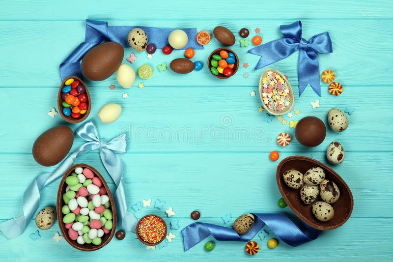 A frame of chocolate Easter eggs, delicious sweets and Easter decorations on a blue background royalty free stock photography