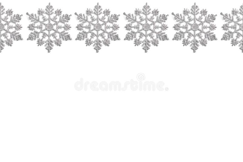 Frame of Christmas decor in the form of silver snowflakes on a white background. new year layout, top view, flat lay royalty free stock photo