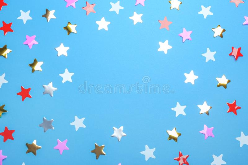 Frame of confetti stars with space for text on blue , top view. Christmas celebration. Frame of confetti stars with space for text on blue background, top view stock photography