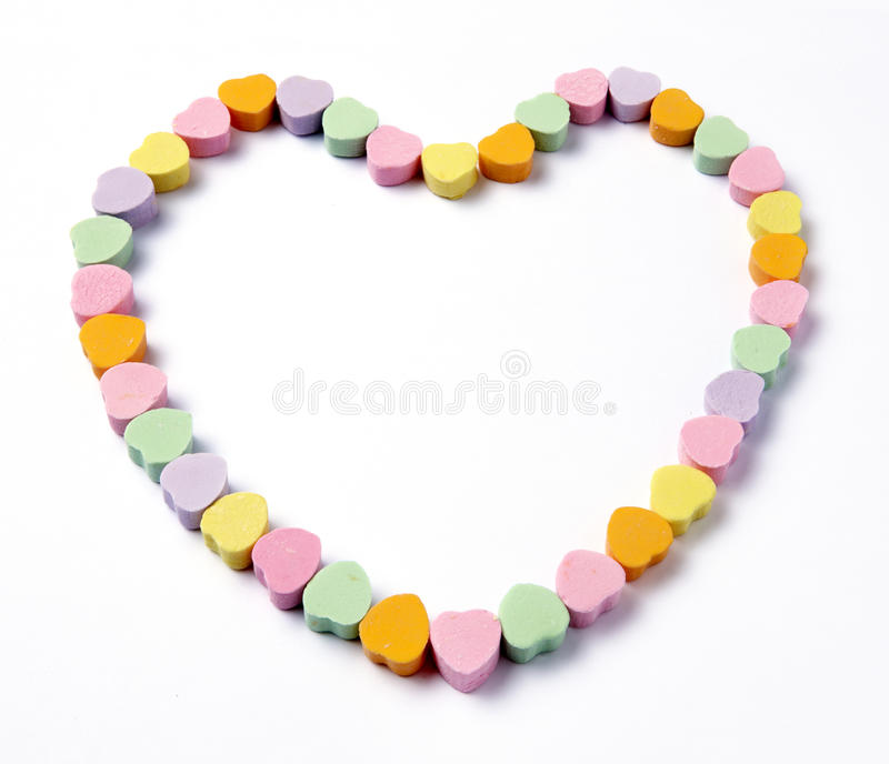 Frame of Conversation Hearts. Conversation hearts in the form of a large heart shot on white with soft shadows and space for copy stock photo