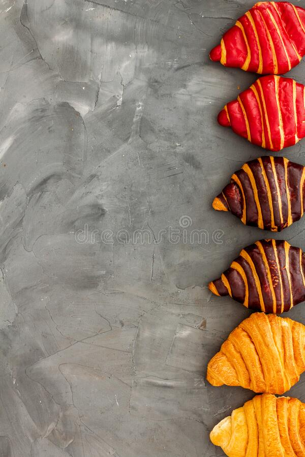 Frame of croissants - fresh bakery on dark stone background. Top view stock photos