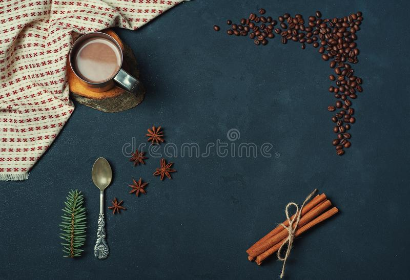 Frame of Cup of Cacao Coffee Beans Cinnamon sticks Spoon and Fir Branch on Dark Texture Table decorated with Napkin. Kitchen royalty free stock photography