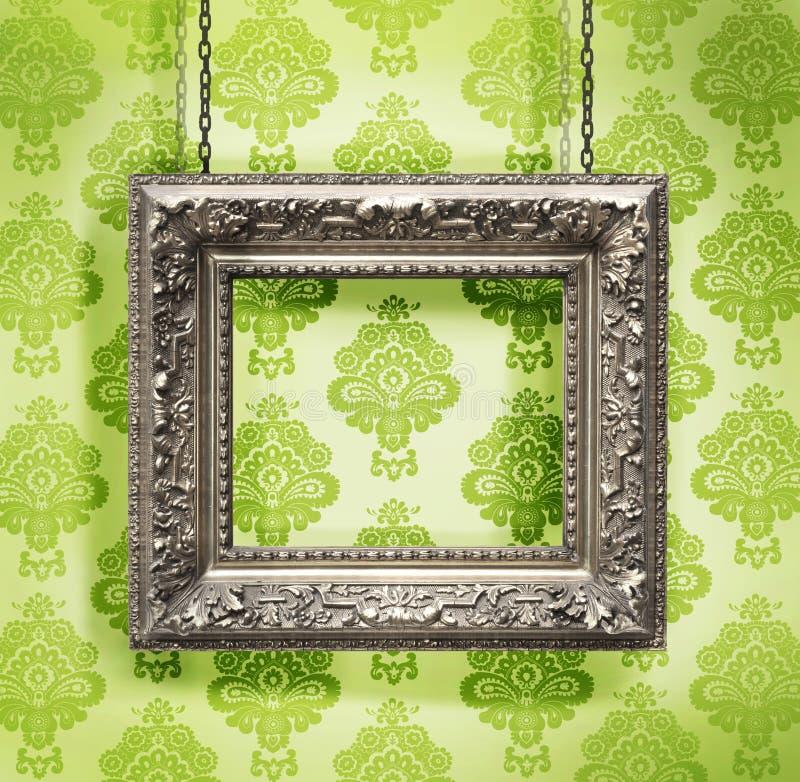 Frame de retrato de prata pendurado de encontro ao papel de parede floral foto de stock