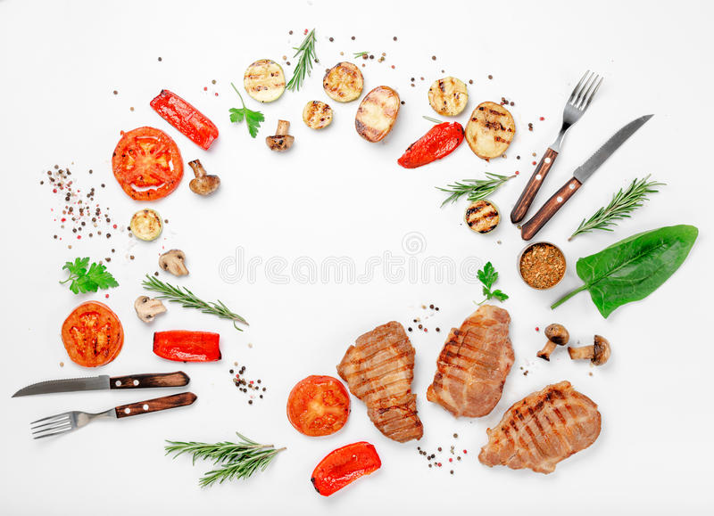 Frame of different food grilled on a white background. Top view. Flat lay royalty free stock photos