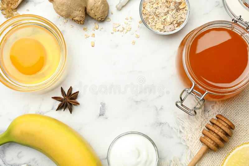 Frame of different ingredients on white marble background, flat lay. Handmade face mask. Frame of different ingredients with space for text on white marble royalty free stock photography
