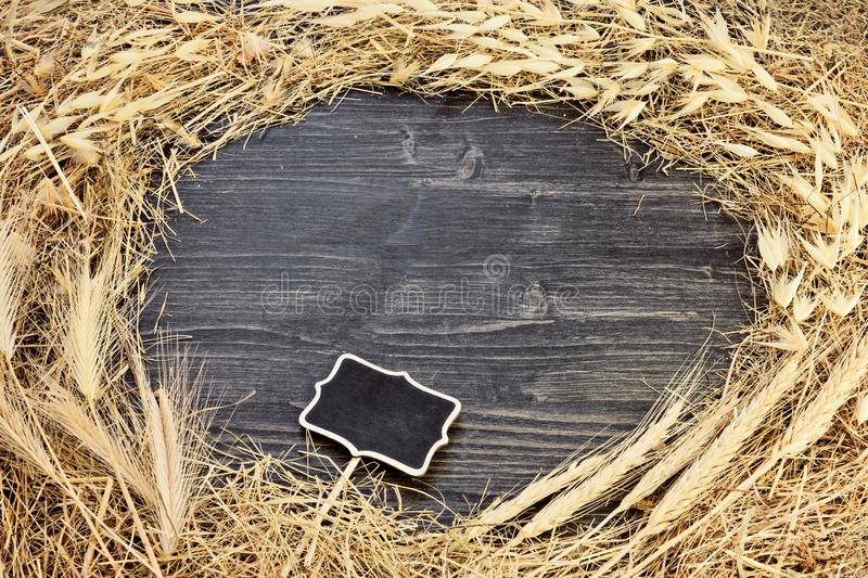 Frame from dry hay grass on dark wooden background with chalkboard tag stock image