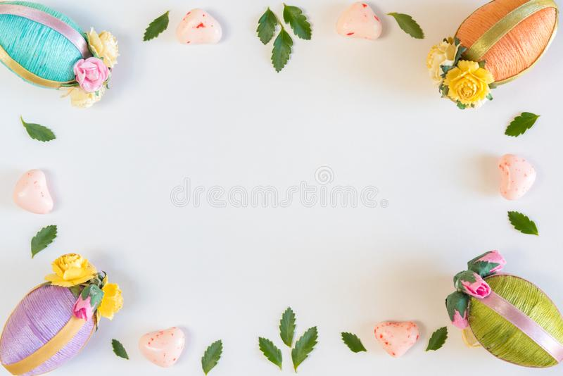 Frame of Easter eggs, leaves, and candy on sold white background royalty free stock photography