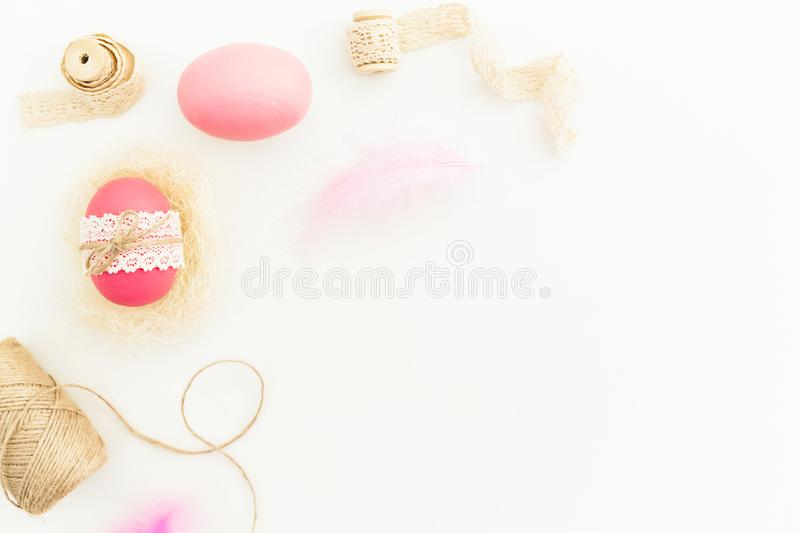 Frame of Easter pink eggs with twine, feathers and tapes on white background, Top view, Fat lay. Easter holiday stock images