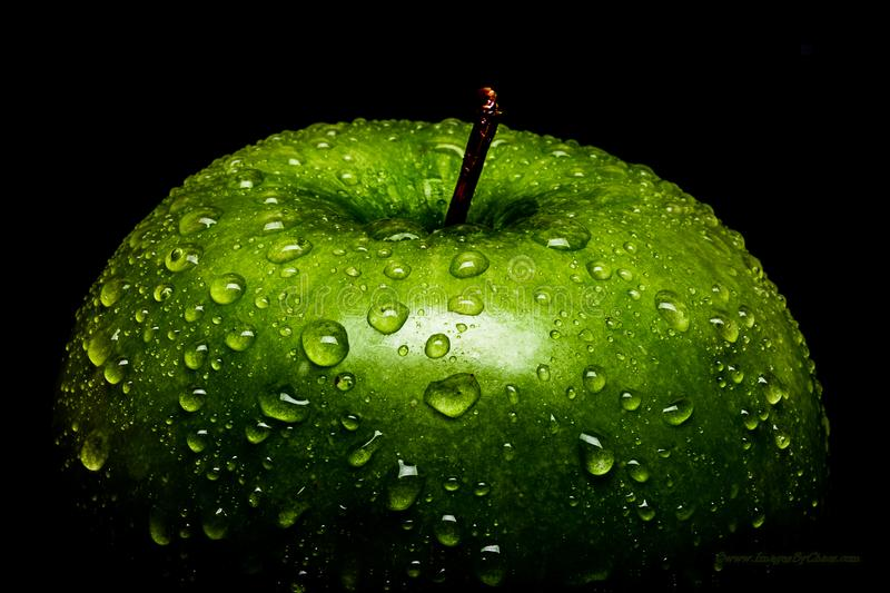 A Frame filling Macro image of a vibrant Green Granny Smith apple covered in water drops beading on the peel. This is a high contrast image with a strong royalty free stock photo