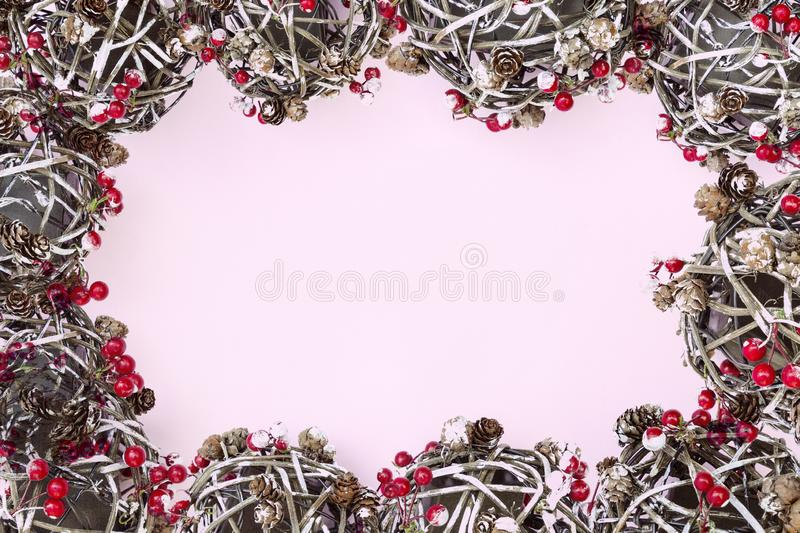 Frame of fir branches, red berries, balls, pine cones, Christmas decoration on pink background. Merry Christmas composition, New stock photography