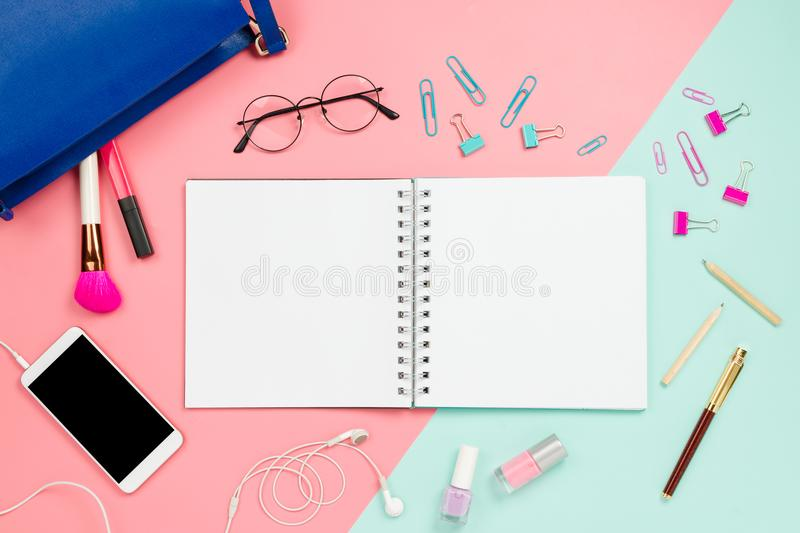 Frame flatlay with woman`s blue bag, glasses, smartphone with black copyspace, cosmetics, stationary supplies and notebook with b. Lank white page. Pastel royalty free stock photos